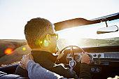 Mature man driving convertible at sunset