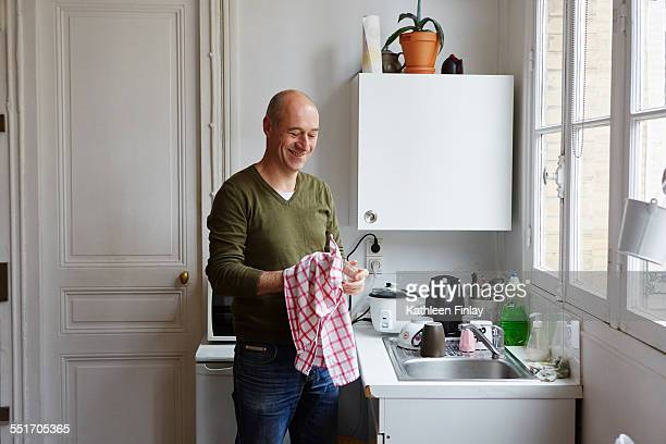 Mature man drying glass at kitchen sink
