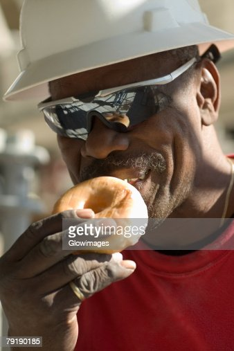 Mature man eating a bun : Foto de stock