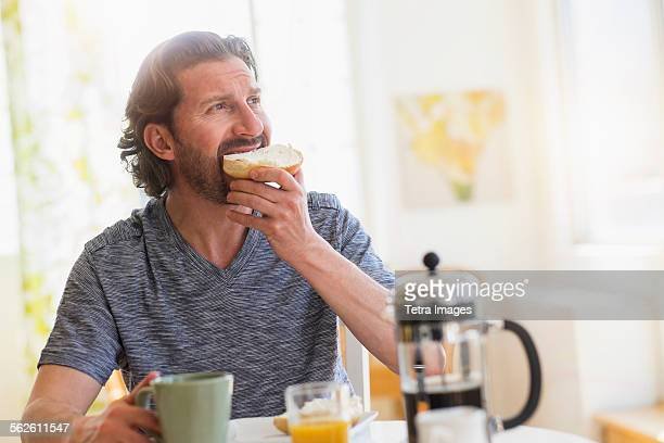 Mature man eating breakfast