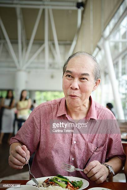 Mature man eating his rice