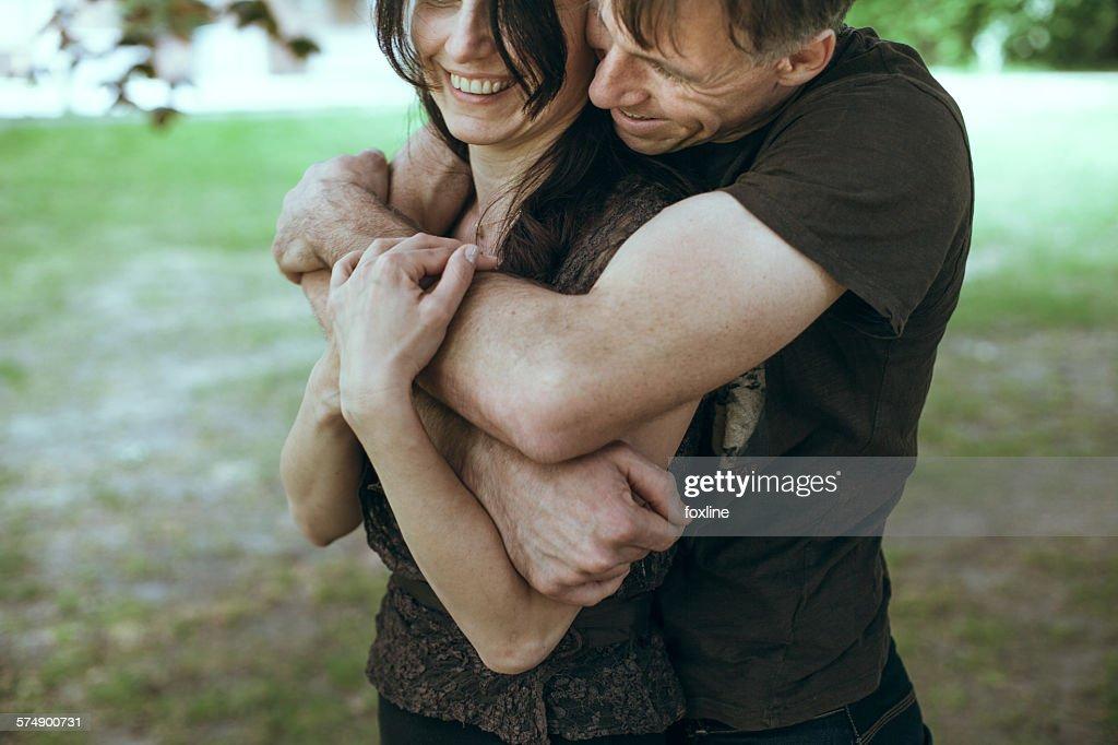 Mature man embracing mature women from behind