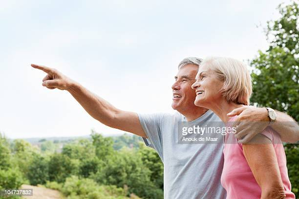 Mature man embracing woman points away