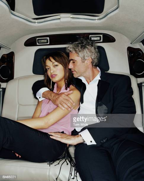 Mature man embracing young woman in back of limousine, portrait