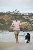 Mature man exercising dog on beach