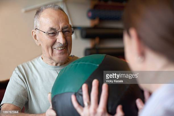 Mature man exercising with physical therapist.