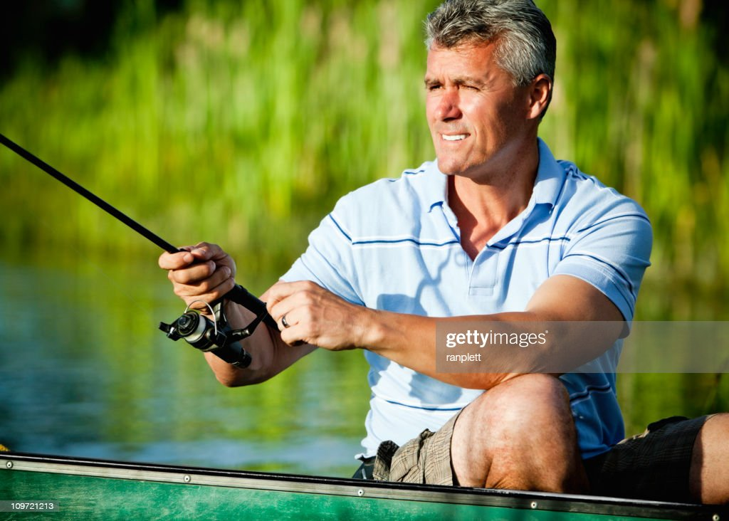 Mature Man Fishing From a Canoe : Stock Photo