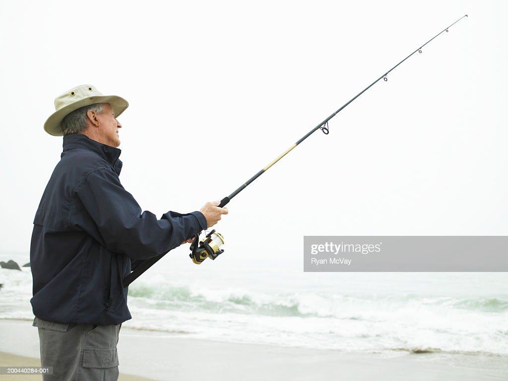 Mature man fishing on beach