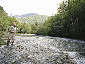 Mature man fly fishing in river, casting line