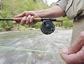 Mature man fly fishing in river, pulling line from reel, close-up