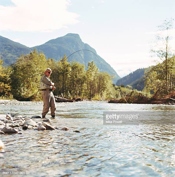 Mature man fly fishing in river, reeling in fish