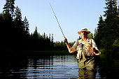 Mature man fly-fishing in river, portrait