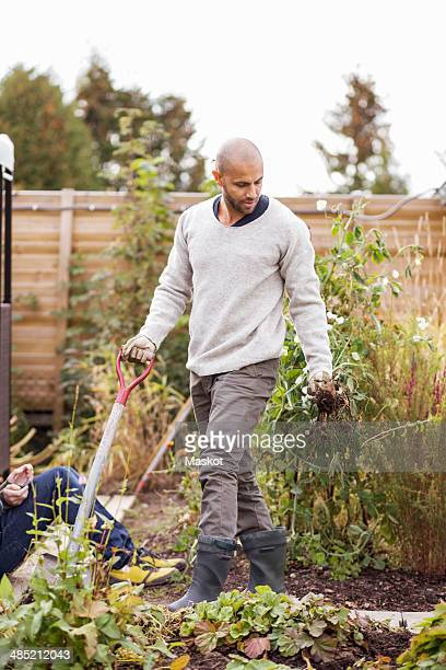 Mature man gardening at yard with children in background