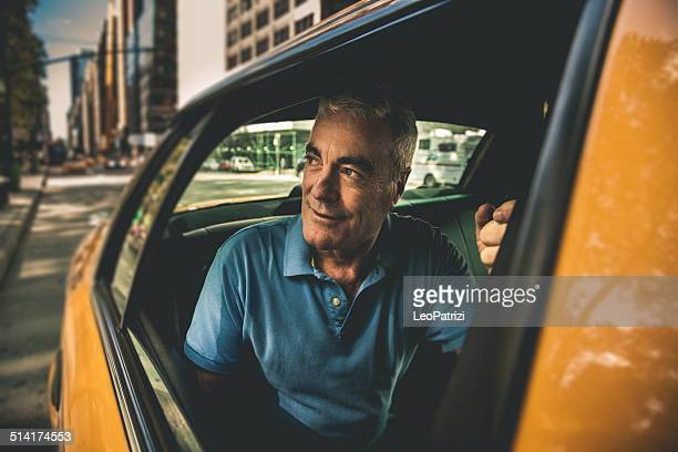 Mature man get on a taxi
