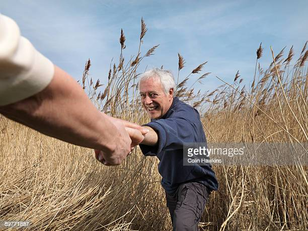 mature man getting helping hand in field