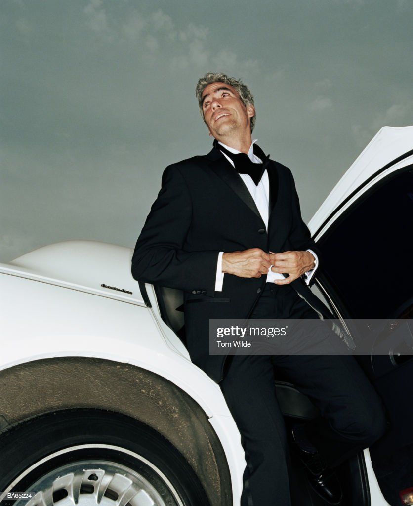 Mature man getting out of limousine fastening jacket, low angle view : Stock Photo