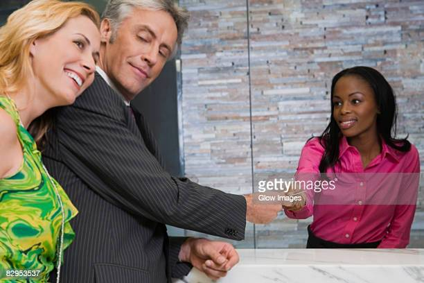 Mature man giving a credit card to a hotel receptionist