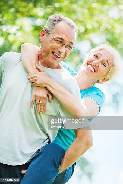 Hombre maduro dando a su esposa a piggyback ride.