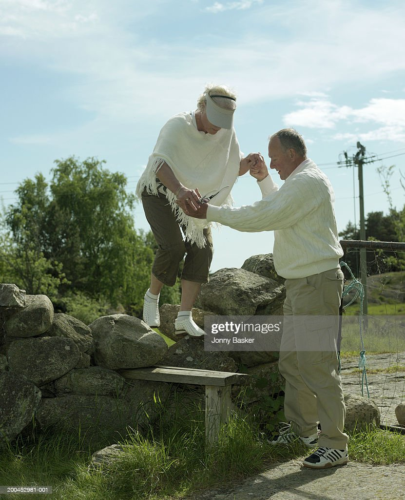Mature man guiding woman over stone wall : Foto de stock