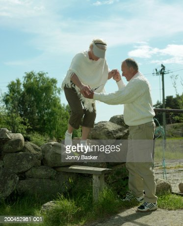 Mature man guiding woman over stone wall : Stock Photo