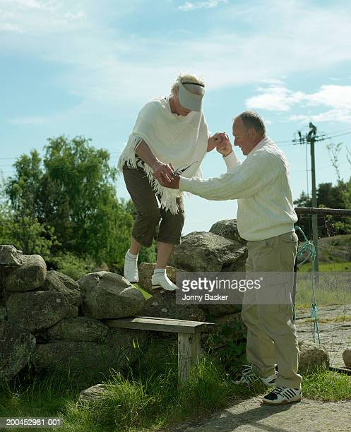 Mature man guiding woman over stone wall