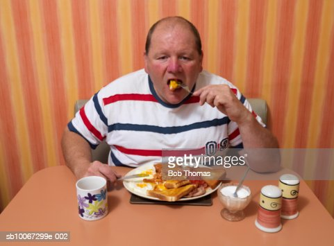 Mature man having breakfast at cafe, portrait : Stock Photo