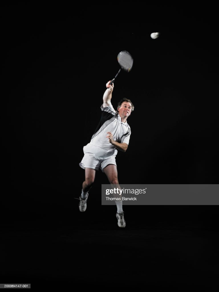 Mature man hitting shuttlecock with badminton racket