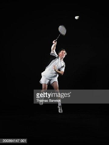 Mature man hitting shuttlecock with badminton racket