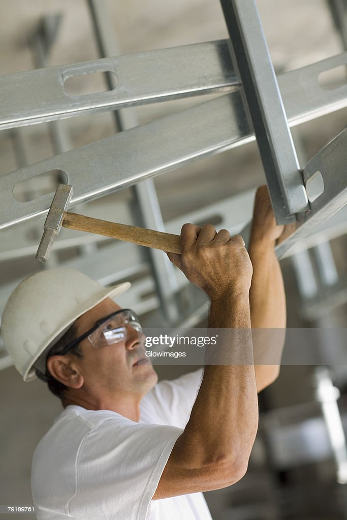 Mature man hitting with a hammer and fixing : Foto de stock