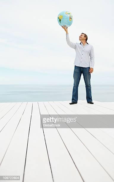 Mature man holding a globe outdoors