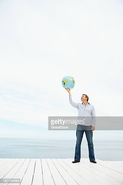 Homem maduro, segurando um globo sobre Cabeça