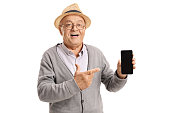 Mature man holding a phone and pointing isolated on white background
