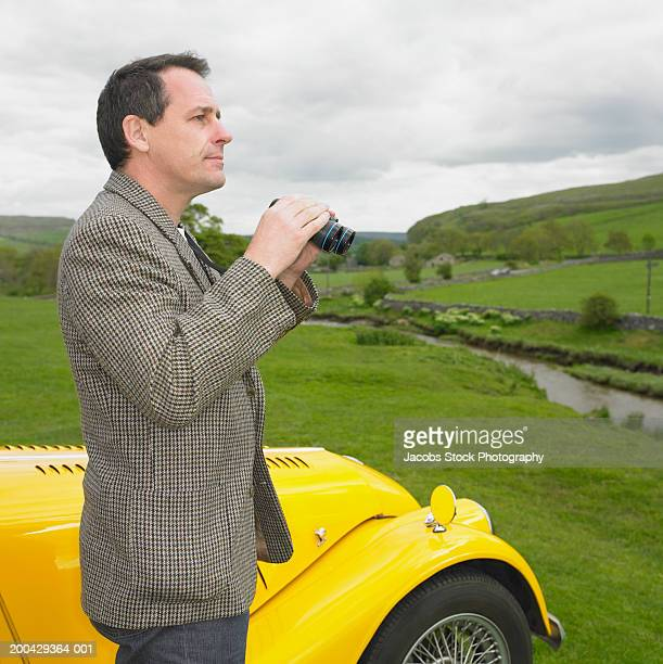 Mature man holding binoculars, side view