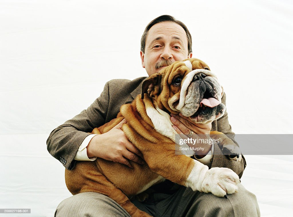Mature man holding  Bulldog, portrait