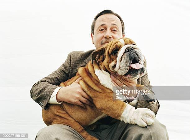 Mature man holding  Bulldog, portrait