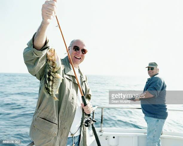 Mature man holding catch (Calico Bass) on deck of boat