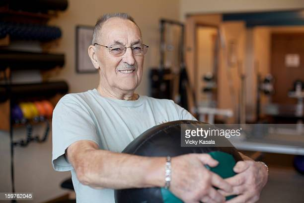 Mature man holding exercise ball at gym.