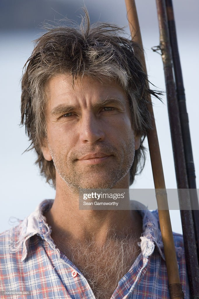 Mature man holding fishing rods, outdoors, close-up, portrait