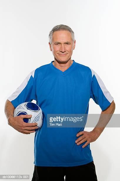 Mature man holding football under arm, smiling, portrait, close-up