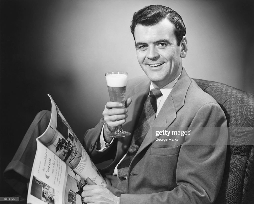 Mature man holding glass of beer and magazine (B&W), portrait : Stock Photo