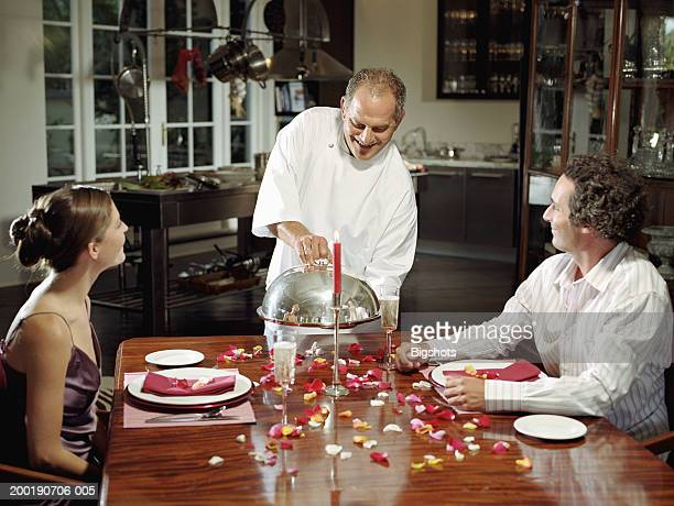 Mature man holding lid on dish by couple at dinner table