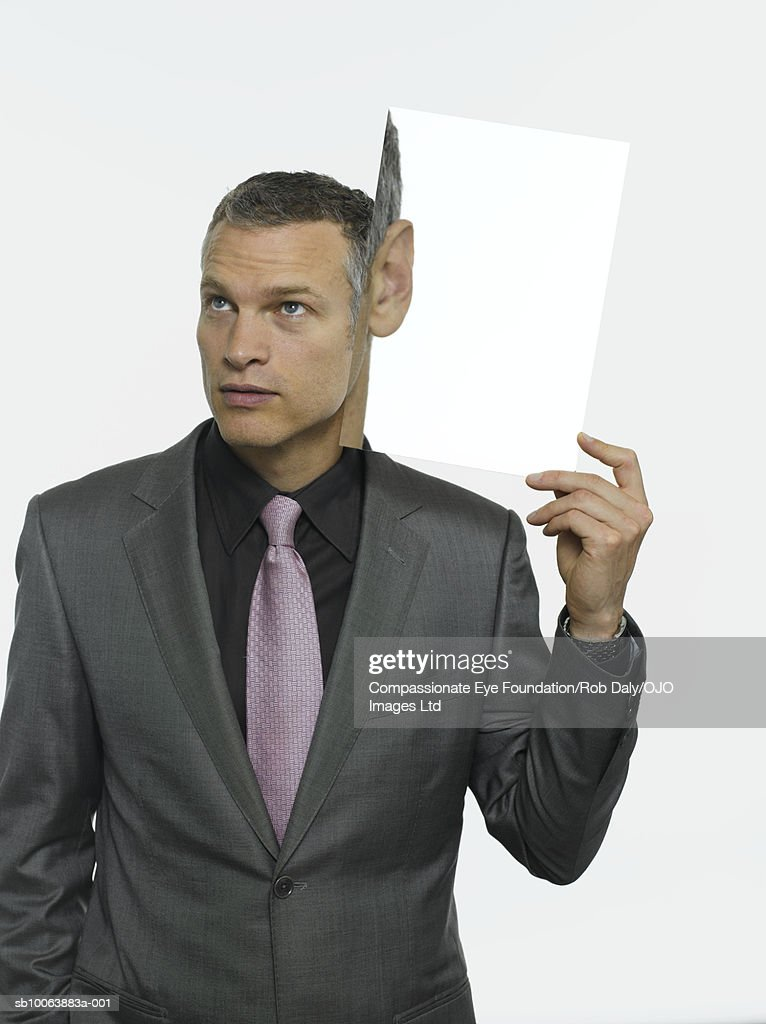 Mature man holding magnified picture of ear : Stock Photo