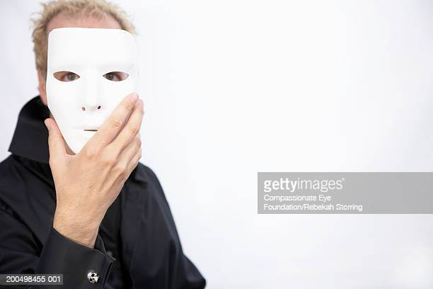 Mature man holding mask in front of face, portrait