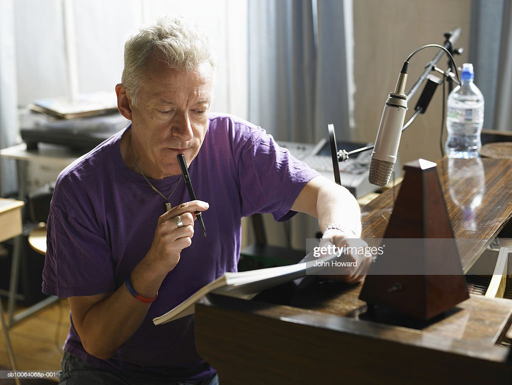 Mature man holding pen to chin, reading
