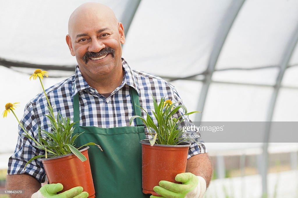Mature man holding plant pots in garden centre, portrait
