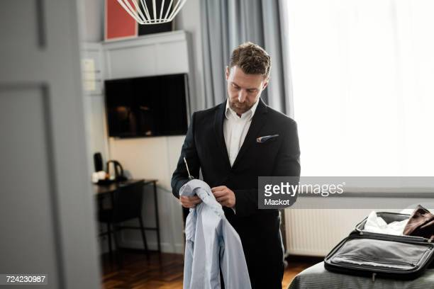 Mature man holding shirt in coathanger standing at hotel room