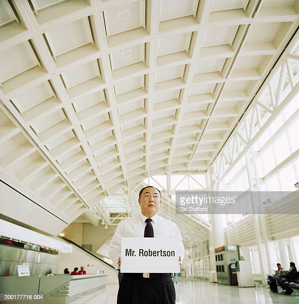 Mature man holding sign in airport