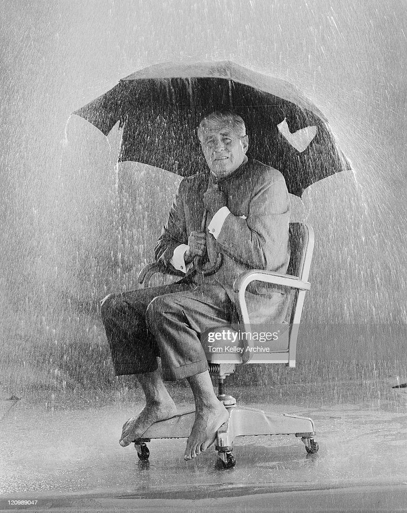 Mature man holding torn umbrella in rain : Stock Photo