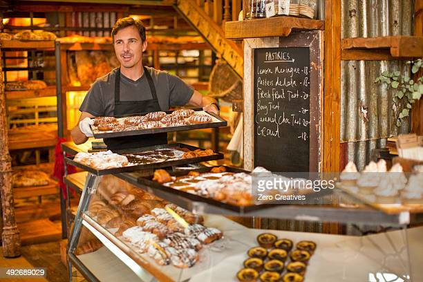 Mature man holding tray of fresh pastries