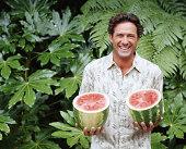 Mature man holding two watermelon halves, laughing, portrait